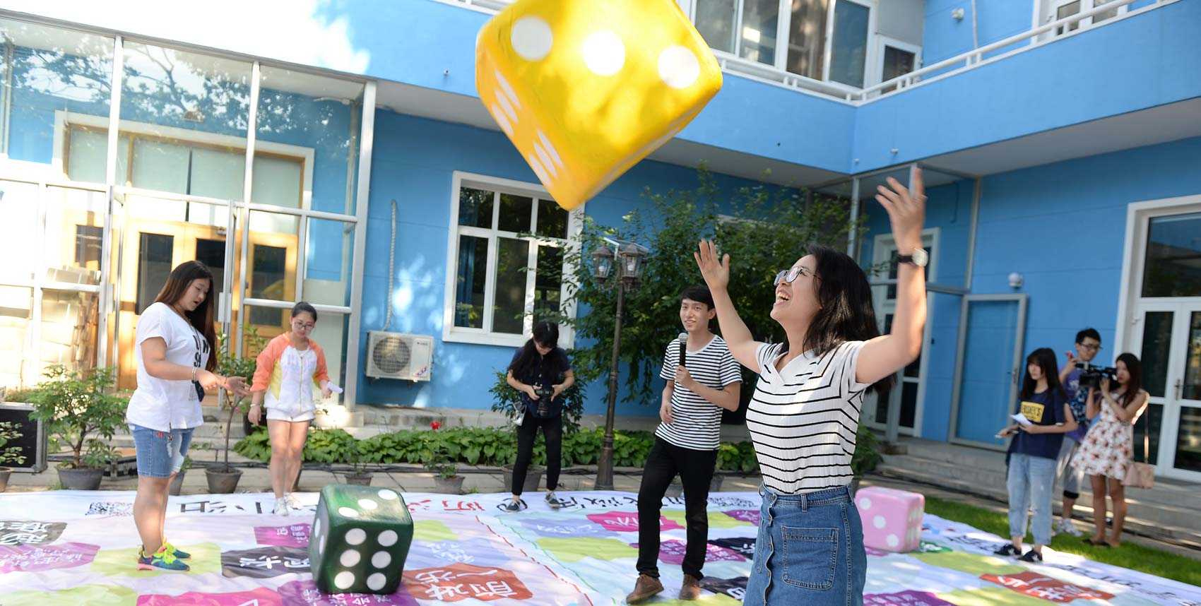 Children play room-sized game in courtyard of school on sunny day