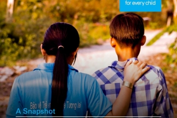 Backs of adolescent boy and girl with hand on one shoulder