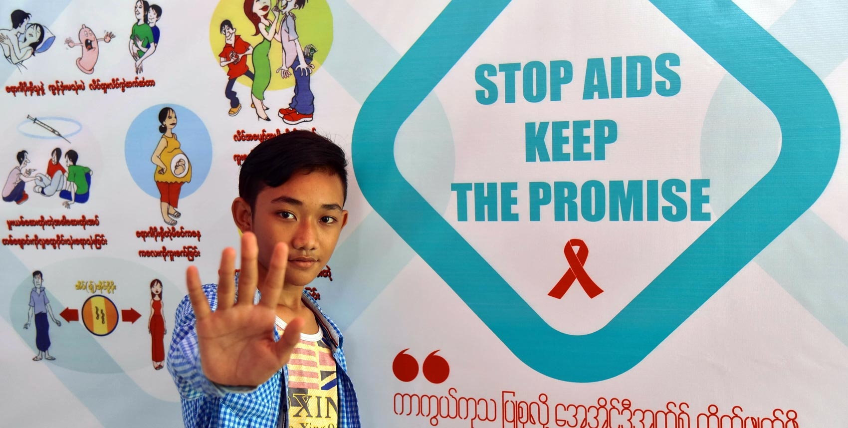 A young man gestures stop in front of a poster that says 'Stop AIDS Keep the Promise'