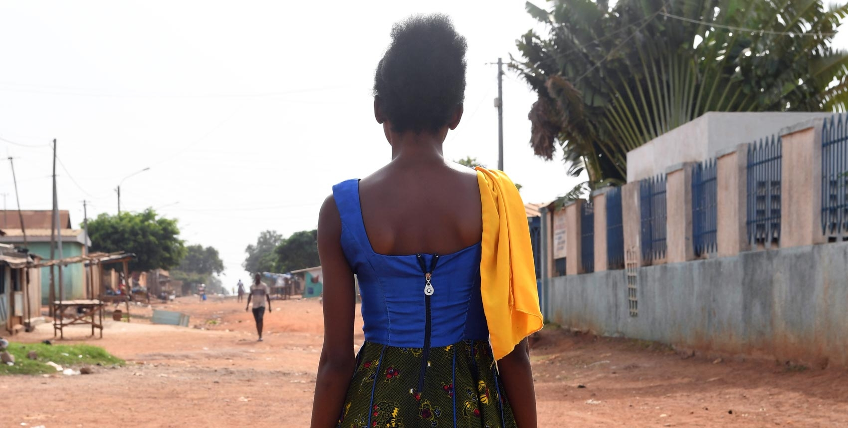 A young woman stands back to camera